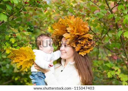 Young beautiful mother in a maple leaf wreath holding a sweet baby girl playing with yellow leaves - stock photo