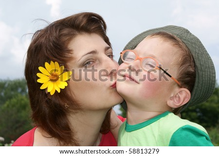 Young beautiful mother kissing her son,background nature - stock photo