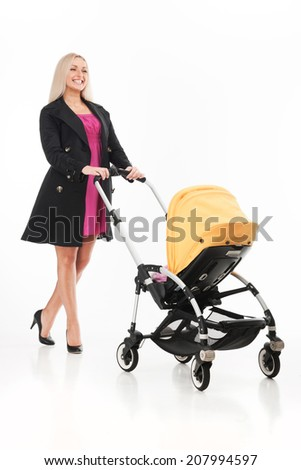 young beautiful mum with baby in stroller. beautiful blond strolling toddler and smiling - stock photo