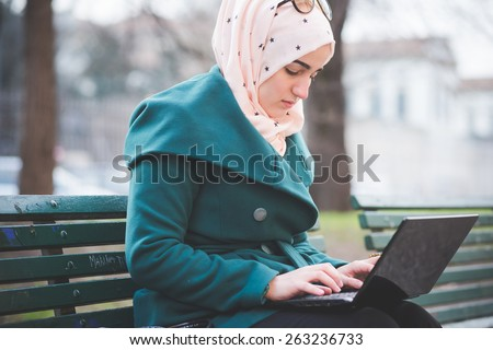 young beautiful muslim woman at the park in spring using notebook connected online working business - stock photo