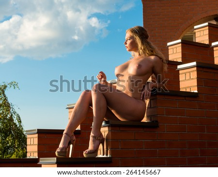 Young beautiful naked woman posing on the stairs - stock photo