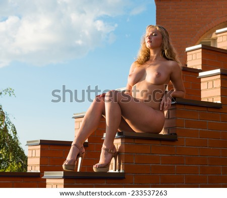 Young beautiful naked woman posing on the stairs in the evening sun - stock photo