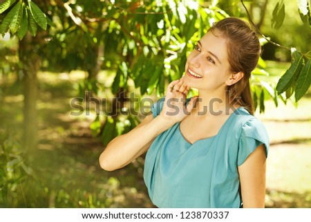 Young beautiful natural woman in the garden (soft focus on eye) - stock photo