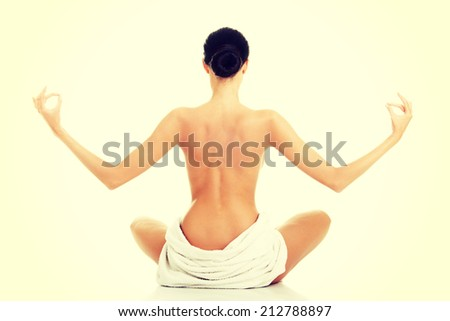 Young beautiful nude woman with towel practicing zoga, isolated on white - stock photo