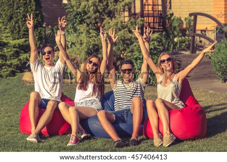 Young beautiful people in casual clothes and sun glasses are keeping hands up, looking at camera and smiling, sitting on bean bag chairs while resting outdoors - stock photo