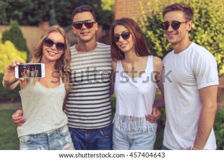 Young beautiful people in casual clothes and sun glasses are making selfie using smart phone and smiling, standing outdoors - stock photo
