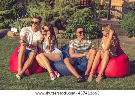 Young beautiful people in casual clothes and sun glasses are sitting on bean bag chairs while resting outdoors. One couple is making selfie, the other is talking - stock photo