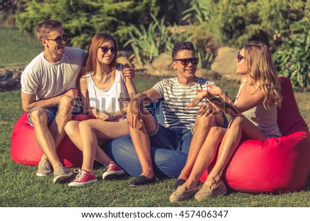 Young beautiful people in casual clothes and sun glasses are talking and smiling, sitting on bean bag chairs while resting outdoors - stock photo