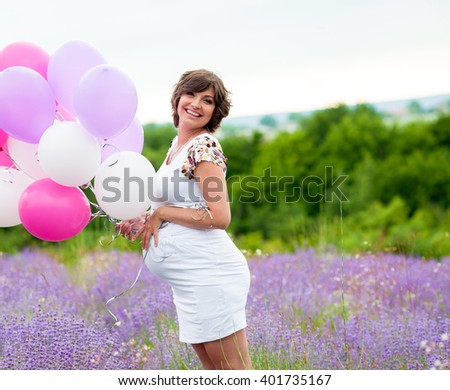 Young beautiful pregnant woman in a field of lavender holding a bunch of balloons - stock photo