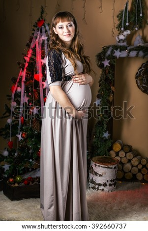 Young beautiful pregnant woman in a long  dress near new year tree . Christmas setting . Studio - stock photo