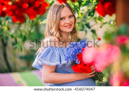 Young beautiful pregnant woman in the garden. Pregnant In the yard. Woman in blue dress. - stock photo