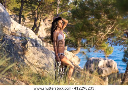 Young beautiful pretty woman standing and posing in bikini or swimwear at forest in sunset light. Fashion style outdoor summer portrait - stock photo