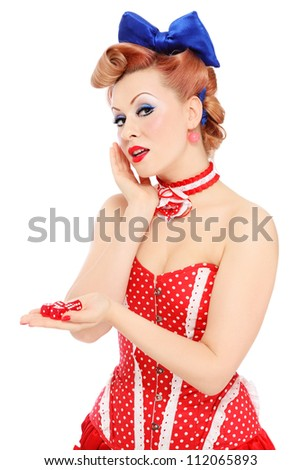 Young beautiful promo pin-up girl in vintage polka dot corset with red dice in hand over white background - stock photo