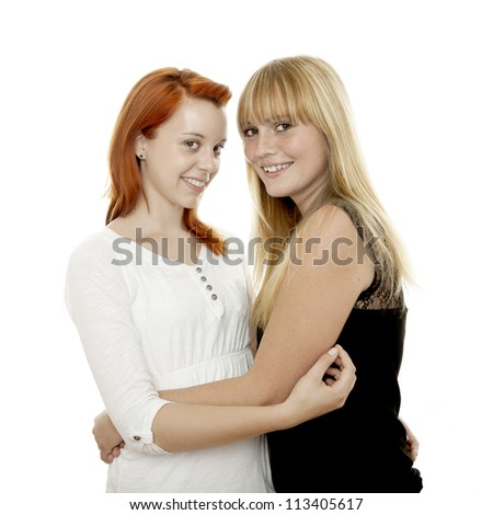 young beautiful red and blond haired girls hugs and smile in front of white background - stock photo