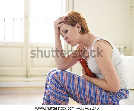 young beautiful red hair woman holding hot water bottle in a hurting belly suffering stomach cramp and period pain sitting on home couch in painful face expression female menstruation concept - stock photo