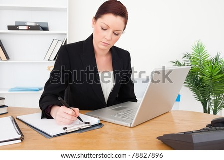 Young beautiful red-haired female in suit typing on her laptop and writing on a notepad while sitting in an office - stock photo