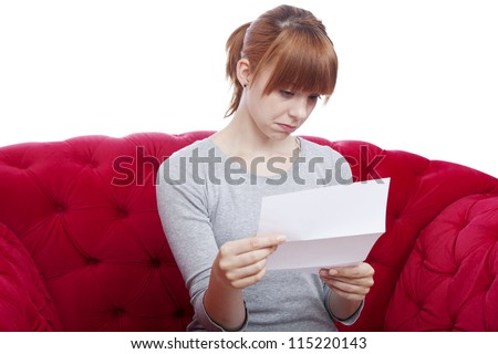 young beautiful red haired girl get bad news on red sofa in front of white background - stock photo