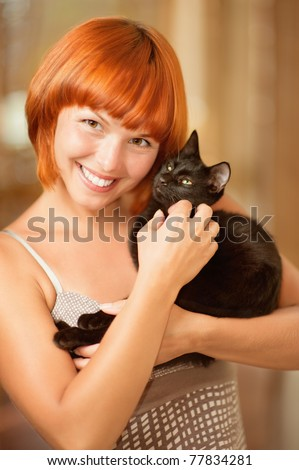 Young beautiful red-haired smiling woman has control over fluffy black cat. - stock photo