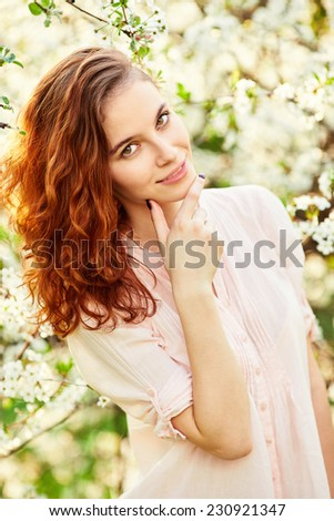 Young beautiful red-haired woman in blooming garden - stock photo