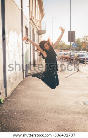 Young beautiful reddish brown hair caucasian woman jumping in the street looking in camera smiling - carefreeness, youth, freshness concept - dressed with blue jeans and black shirt - stock photo