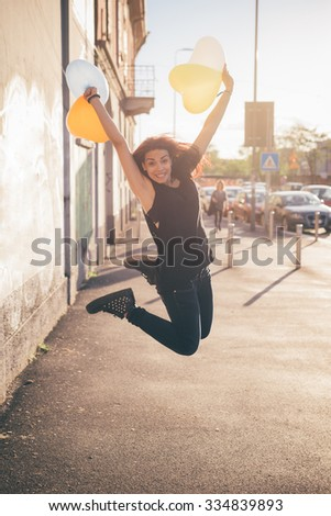 Young beautiful reddish brown hair caucasian woman jumping, in the street looking in camera smiling playing with balloon in shape of heart - carefree, youth, freshness concept - stock photo