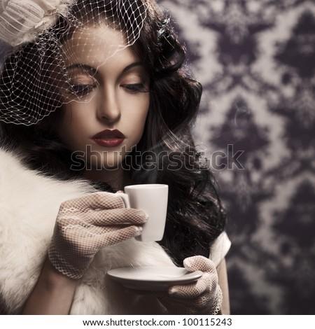 Young beautiful retro lady drinking coffee - stock photo