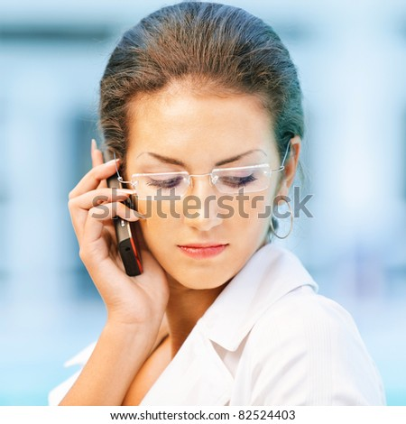 Young beautiful sad business woman in glasses talks by mobile phone and looks downwards against magnificent office. - stock photo
