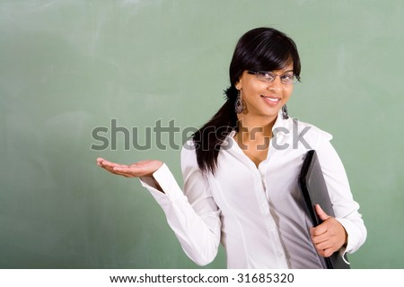 young beautiful school teacher in front of blackboard - stock photo