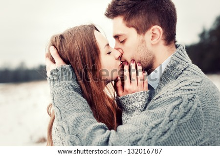 Young beautiful sensual couple outdoor portraits. Boy and girl having fun in cold weather. - stock photo