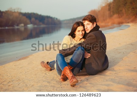 Young beautiful sensual stylish couple in love sitting on sand near the river - stock photo