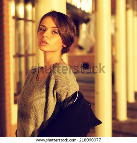 young beautiful sensual woman in gray pullover taking off her black coat in attractive exterior or location in sunset lightning - stock photo