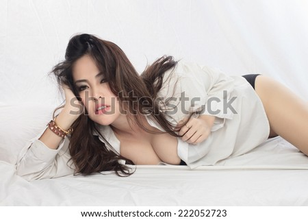 Young beautiful Sexy Asian woman posing on bed - stock photo