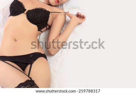 Young beautiful Sexy Asian woman wearing elegant lingerie posing on bed - stock photo