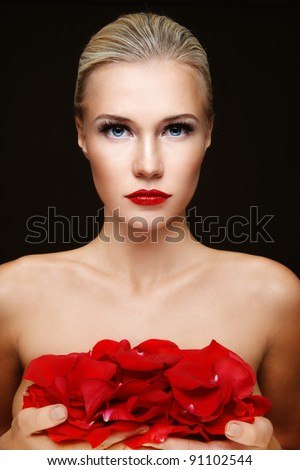 Young beautiful sexy blond woman with red rose petals in hands - stock photo