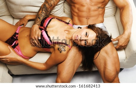 Young beautiful sexy couple in underwear lying on sofa - stock photo