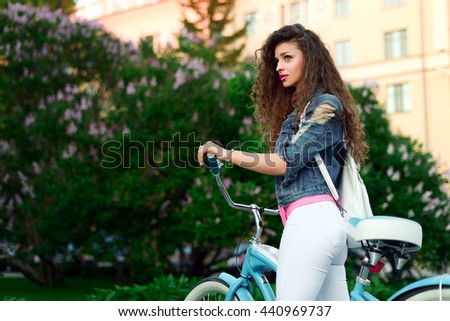 Young beautiful sexy girl with curly hair and a beautiful smile rests in the Park on a bicycle in summer - stock photo