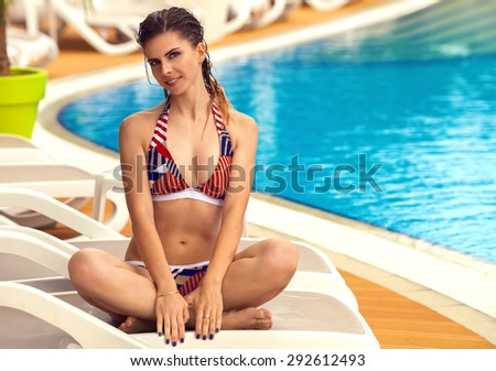 Young beautiful sexy sporty woman with fitness muscular body in swimsuit relaxing at swimming poolside. Sport active lifestyle. Background with copy space - stock photo