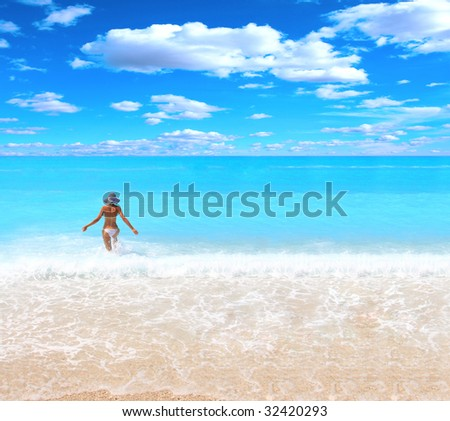 Young beautiful sexy tanned blond woman in hat and bikini in the sea - stock photo
