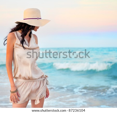 Young beautiful sexy tanned brunette woman wearing straw hat and elegant dress posing standing on beach near waves and looking away at the sea - stock photo