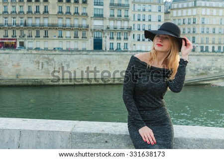Young beautiful sexy woman in a hat on a bridge in Paris - stock photo