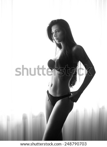 Young beautiful sexy woman in black lingerie posing in window light near curtains. Sensual brunette long hair female with perfect body staying near a window. Attractive girl, black and white photo - stock photo