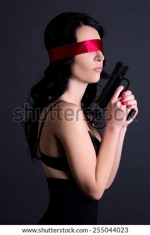 young beautiful sexy woman in black lingerie with red ribbon on eyes holding gun over grey background - stock photo