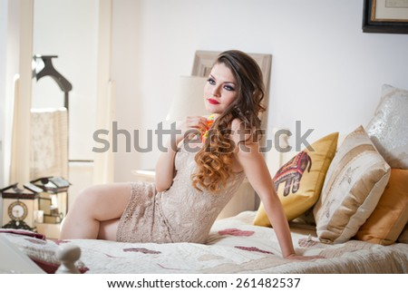 Young beautiful sexy woman in white short tight dress posing challenging indoor on vintage bed. Sensual long hair brunette in bedroom. Attractive female lying provocatively on bed full of pillows - stock photo
