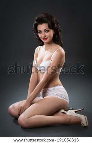 Young beautiful sexy woman sitting on a floor over dark background - stock photo