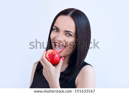 Young beautiful sexy woman smiling and licking red apple. Black underwear. Sensual Red Lips. Red Manicure and Lipstick. Desire. Isolated on white. - stock photo