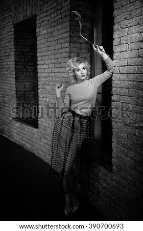 Young beautiful short hair blonde woman in grey dress smoking a cigarette. Elegant romantic mysterious lady with movie star look, brick wall on background. Retro style blonde with cigarette - stock photo