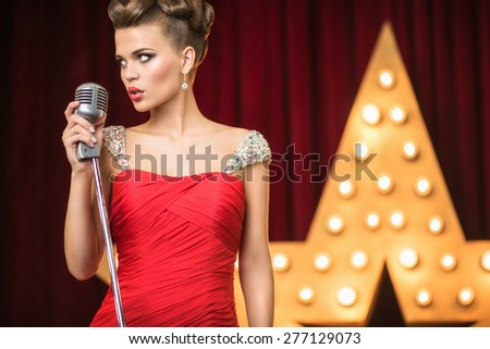 Young beautiful singer on the scene - stock photo