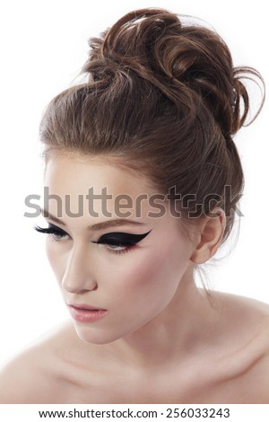 Young beautiful slim woman with fancy cat eye make-up and stylish hairdo over white background - stock photo