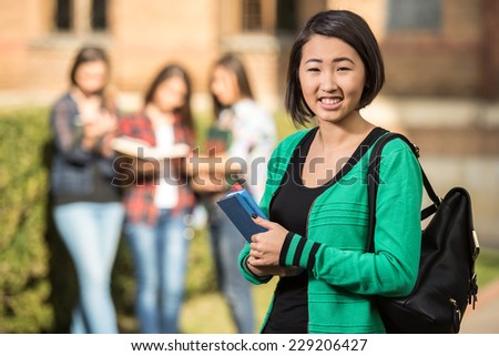 Young beautiful, smiling, asian girl, student at the college.  Her classmates in the background. - stock photo
