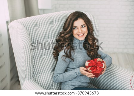 Young beautiful smiling brunette with long curly hair sitting in a chair and holding a gift. - stock photo